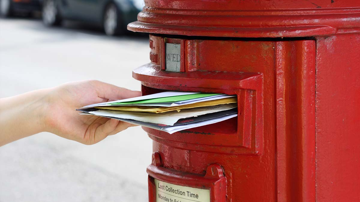 Stuffed mail in Royal Mail postbox.