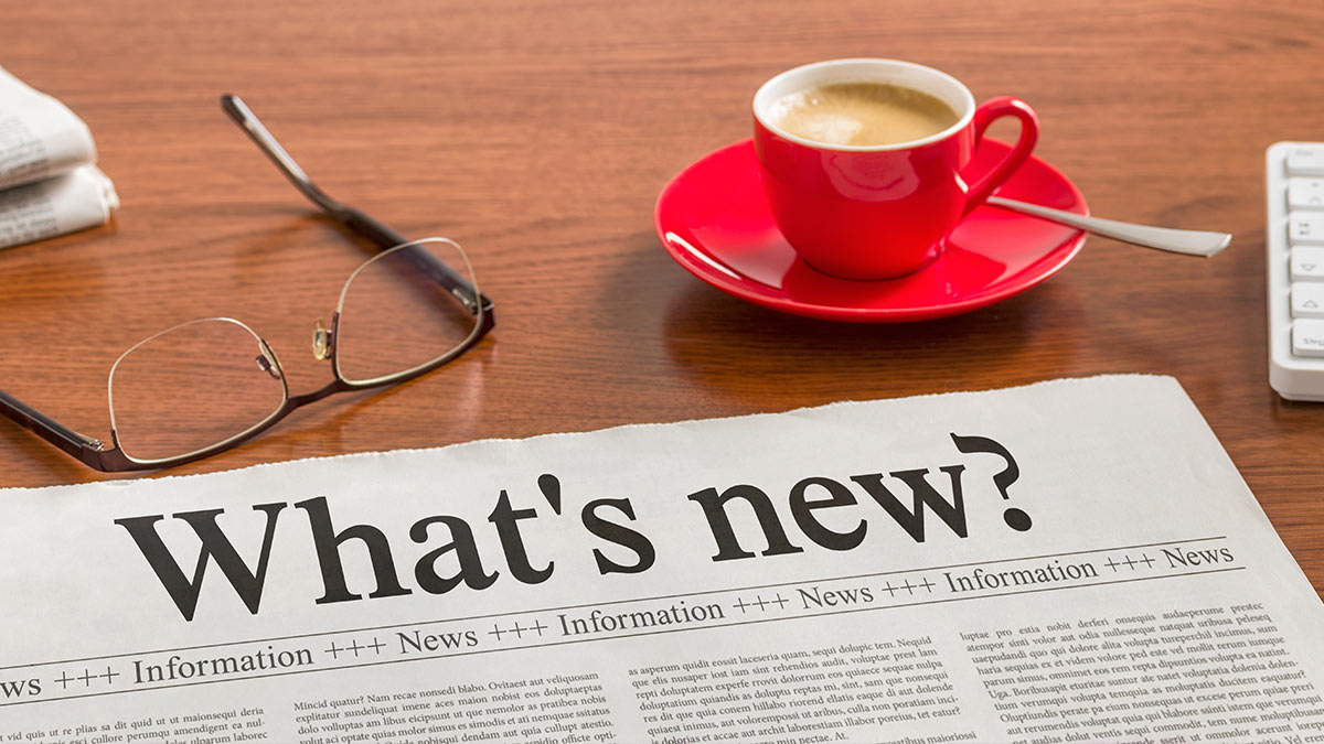 Image of newspaper, reading glasses and a small red cup of coffee.