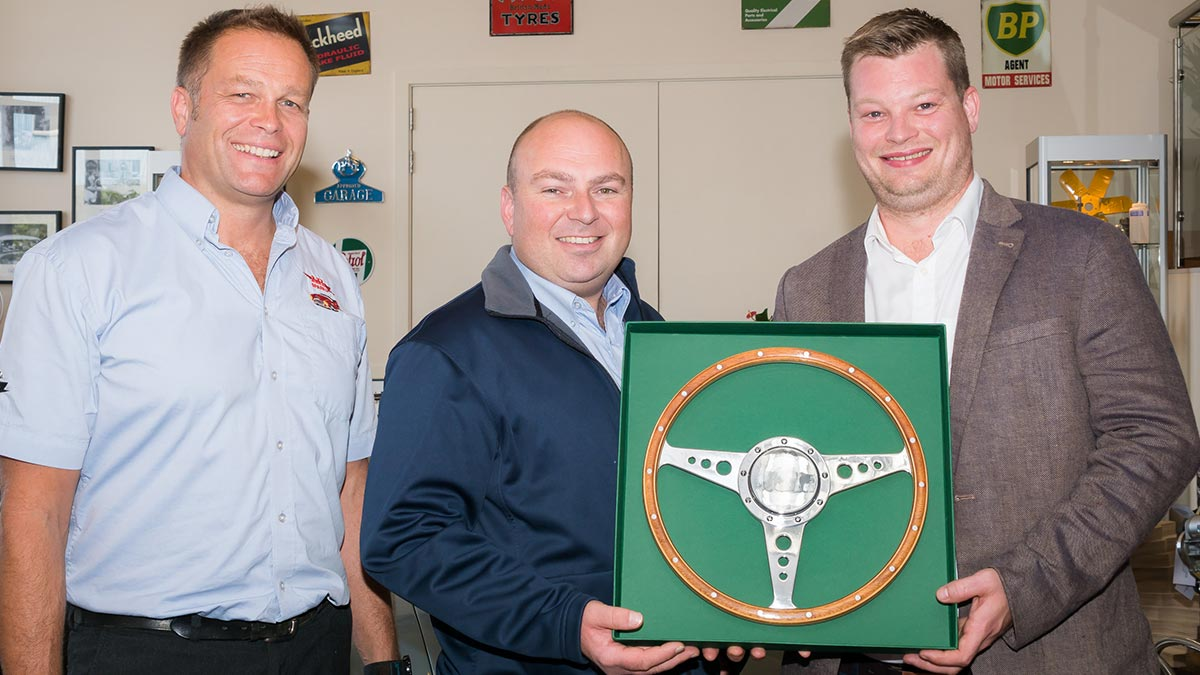 Marcus Poole from Moto-Lita presenting the 60th anniversary commemorative Moto-Lita steering wheel to Jonathan Hill and John Lee.