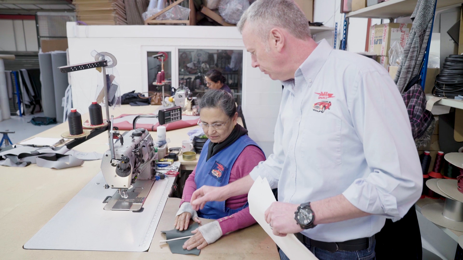Screenshot from corporate film. A.H. Spares Trimmer finishing an Austin-Healey upholstery vinyl sample for a customer.