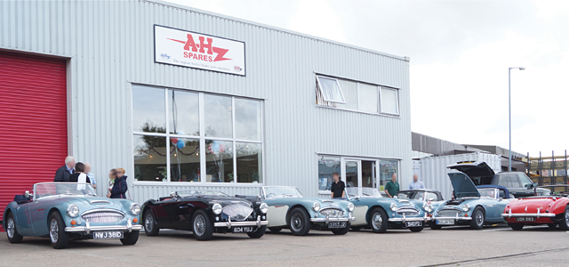 Exterior of A.H. Spares with 7 Austin-Healeys parked outside