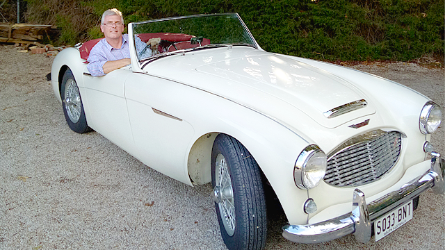 Image of Matthew Randell sitting in his white Austin Healey 100/6