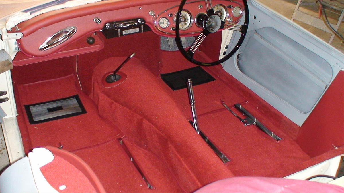 Restored interior of an Austin Healey 100/6 with new red carpets.