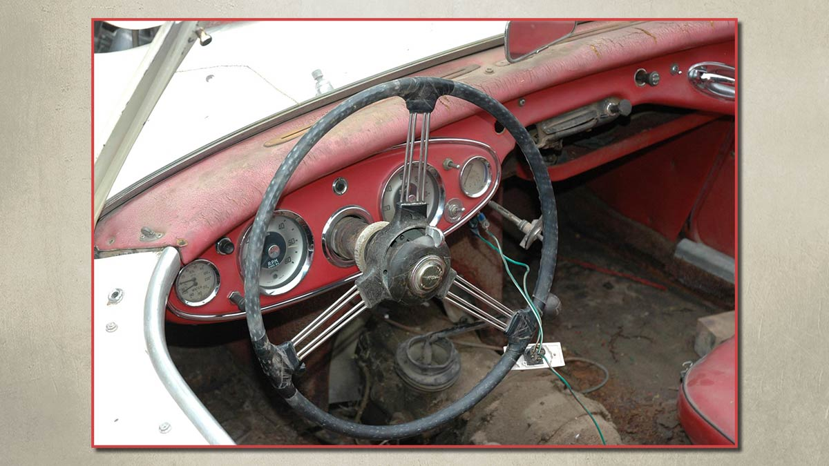 Dashboard and steering wheel of an unrestored Austin Healey 100/6.